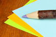 Colorful wooden pencil with sheets of paper on wooden table