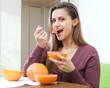 long-haired girl eating grapefruit
