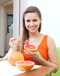 woman eating grapefruit at home