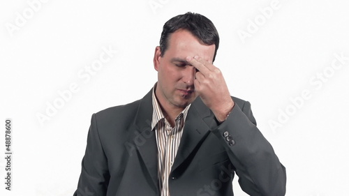 Businessman showing painful grimace and taking medicine