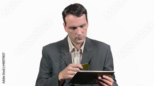 Businessman entering credit card data on his tablet