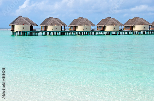 over water bungalows in blue ocean lagoon