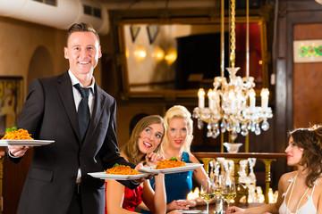 Friends in restaurant, waiter served the dinner