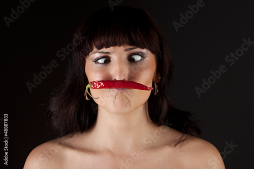 beautiful woman eating hot spicy chili pepper