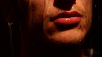 ragazzo sotto la doccia (particolare labbra bagnate)