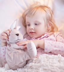 Cute little blond girl play with toy rabbit in bed. Looking ill.