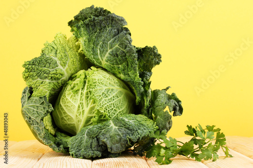 Fresh savoy cabbage on wooden table on yellow background