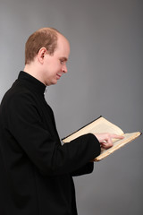 Young pastor with Bible, on gray background