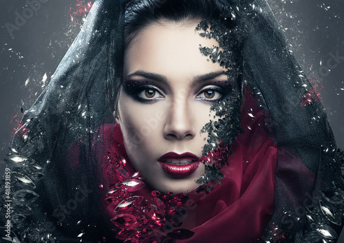 mysterious woman in black hood with gemstones