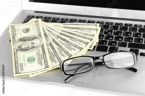 Money with glasses on laptop close-up