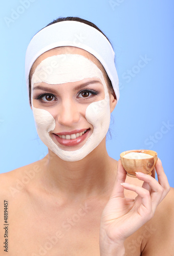 Young woman with clay facial mask, on blue background