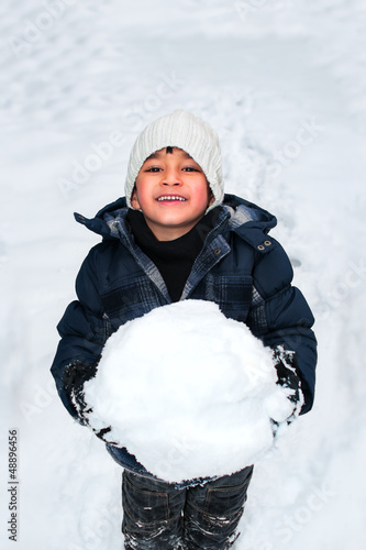 Young happy kid playing with a big snow ball