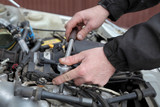 Mechanic servicing engine, ratchet and spark plug