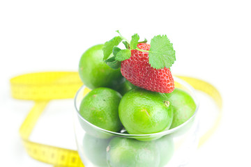 lime in a glass cup, measuring tape, strawberry and mint isolate