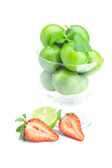lime in a glass bowl, strawberry and mint isolated on white
