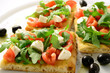 Focaccia with tomatoes, rocket, mozzarella and olives