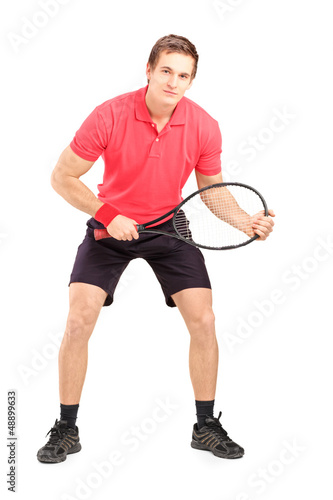 Full length portrait of a male tennis player holding a racket