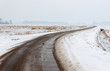 Curved and wet country road in a bald snow landscape