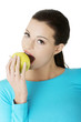 Attractive young woman eating green apple.