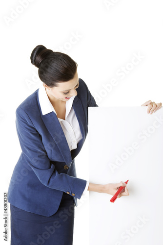 Businesswoman holding blank board and marker.