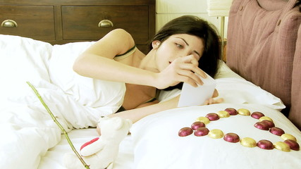 Beautiful woman receiving love gifts in bed