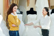 saleswoman helps girl chooses white bridal gown