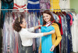 woman chooses evening dress at clothing shop