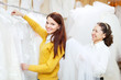 Female consultant helps bride  at shop