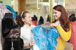 buyers chooses evening dress in the store