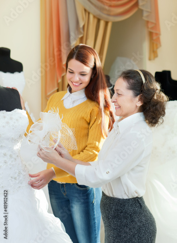 saleswoman helps bride chooses bridal gown