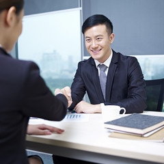 asian business people shaking hands in office