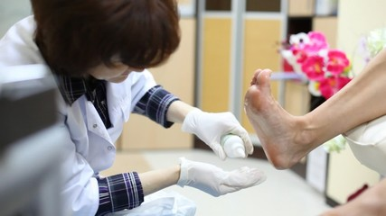 Cosmetician does pedicure to woman and rubs cosmetic oil in its