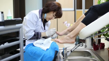 Cosmetician does pedicure to woman and has spread on knees towel