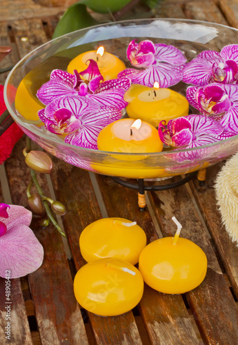 bowl with orchids and candle on wooden table