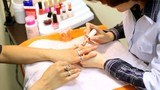 Cosmetician accurately covers nails of client with transparent poster
