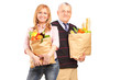 A smiling woman and gentleman holding a paper bag full of grocer