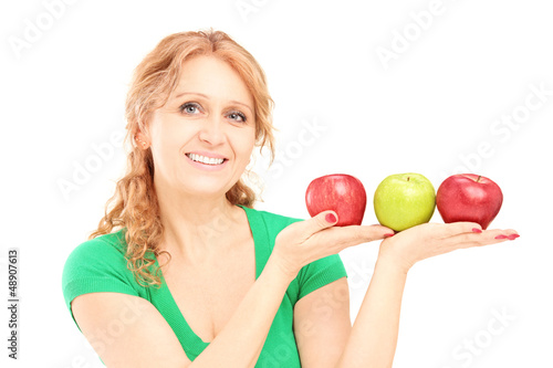 Mature beautiful woman sitting and holding three apples