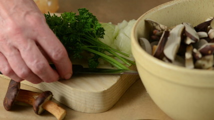 Putting a bunch of parsley herb on board with knife and onion