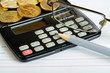 Calculator, glasses, coins and pencil