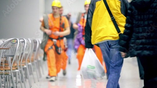 Workers walk among people in cafe, unfocused view
