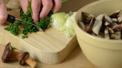 Slicing parsley herb into small pieces to cook mushrooms
