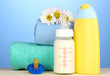 Baby bottle of milk and shampoo near towels on blue background