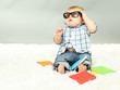 Little boy with multicolor books, on white carpet