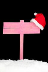 Wooden road sign with Santa hat black background