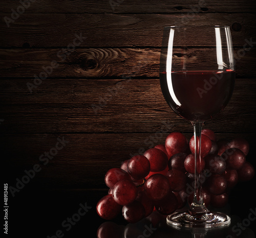 Red wine with grapes and barrel