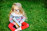 Little girl with a book in a park wearing glasses portrait