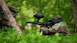 Boy paintball player sits in ambush with gun at background of