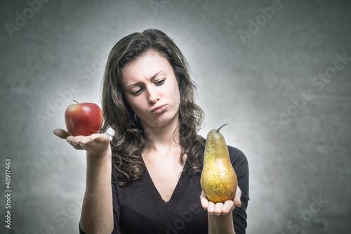 Junge Frau vergleicht Apfel und Birne