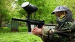 Boy with paint mark on helm holds paintball gun