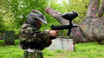 Boy in camouflage stand in shooting position and put paintball